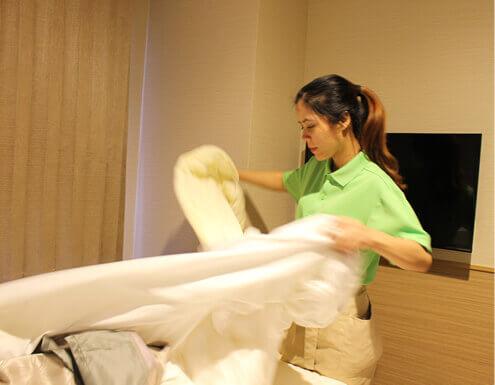 スタッフによるベッドメイキングの様子の写真